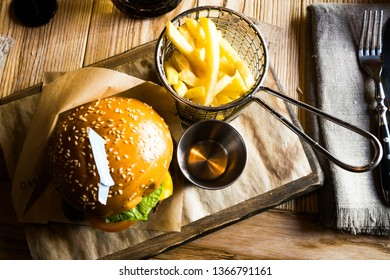 Burger and fries on wooden board on dark wooden background,fresh Big burger on a wooden board with salad, sauce plate and french fries, top close up view