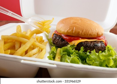 Burger and fries portion in takeout food box with plastic fork , closeup