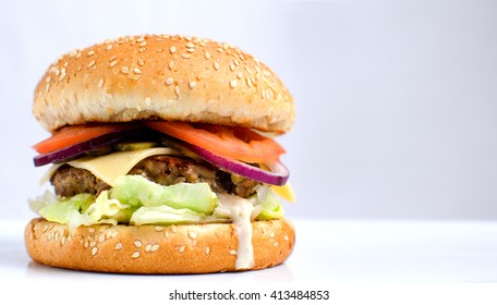Burger full face with vegetables, spices and fries. Meat hamburger. Hamburger with knife. Beef hamburger. Organic hamburger