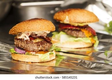 Burger full face with vegetables, spices and fries. Meat hamburger. Beef hamburger. Organic hamburger, burger cooking process,