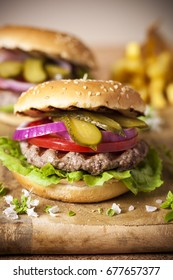 Burger with grilled meat and fresh vegetables on a wooden Board.
