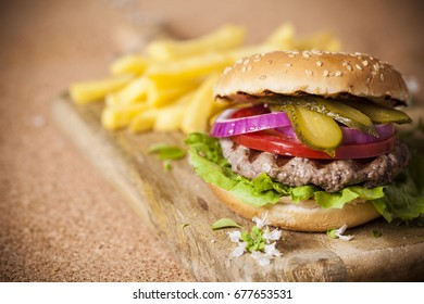 Burger with grilled meat and vegetables closeup. On wooden background with potatoes; selective focus