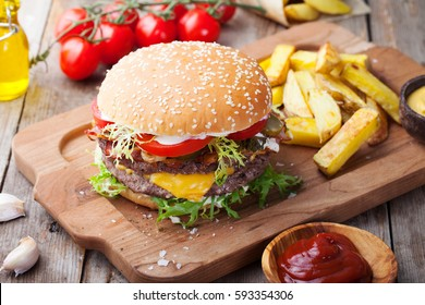 Burger, hamburger with french fries, ketchup, mustard and fresh vegetables on a cutting wooden board.