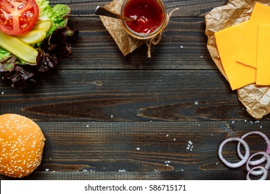 burger ingredients and sauce with copy space on the wooden black table.