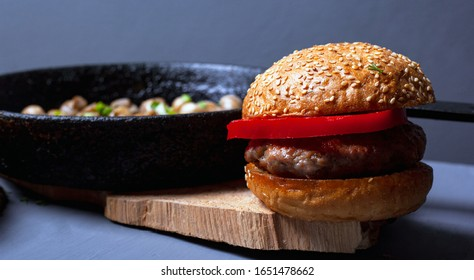burger with a juicy cutlet tender bun and champignon mushrooms in a castiron pan on a wooden rustic plate on a gray background. hearty lunch closeup.
