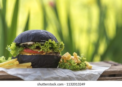 Burger made with black charcoal bun served with potato wedges, lettuce and sauce on wooden rustic table Close up, shallow depth of the field.