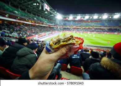 Burger in man hand and stands during football match at evening stadium