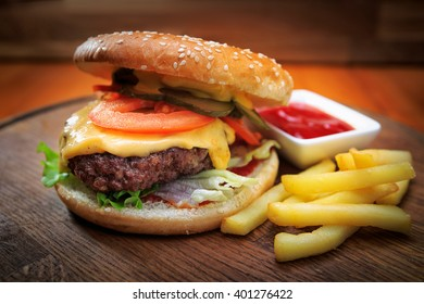 Burger with meat and fried potatoes on a wooden board