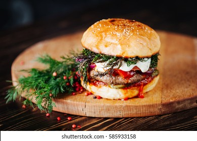 Burger with  meat, tomato, dill and cheese sauce on wooden background. Close up. Copy space