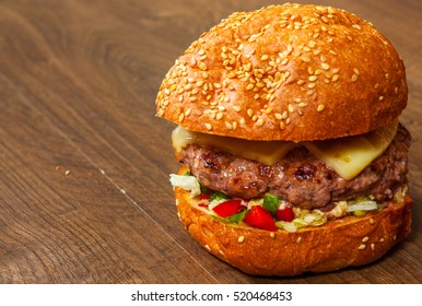 burger with meat, tomato, onion, cheese, lettuce, vegetables on wooden table. with copy space.