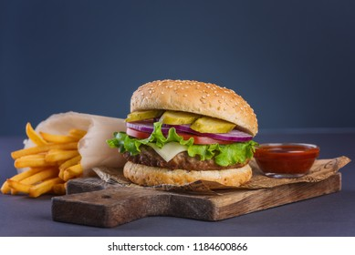 burger with a meatball and fries on a wooden board