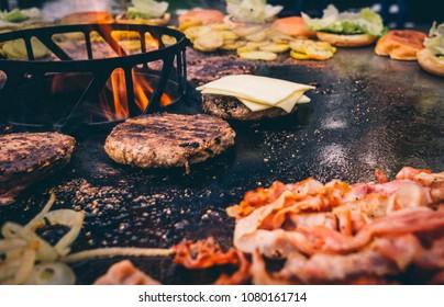 Burger mit Bacon grillen auf der Feuerplatte
