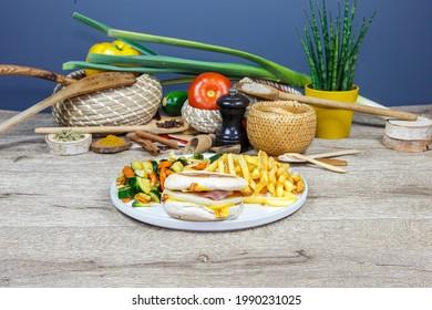 Burger au pain muffin, oeufs, fromage et bacon accompagné de frites sur une assiette blanche, servie sur une planche en bois. Décoration sur fond de légumes.
