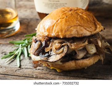 Burger with mushrooms, fried onions and cheese on rustic background