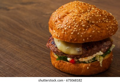 burger on the brown wooden table background. rustic kitchen table with copy space