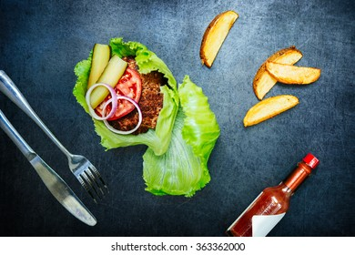 Burger on salad leaves without bread or bun. Served with chili sauce and fried potato
