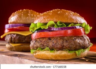Burger on wooden background. Vintage home made burger. Fast food meal. American food.