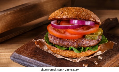 Burger on wooden background. Vintage home made burger. Fast food meal. American food.