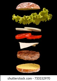 Burger parts flying in air isolated on black