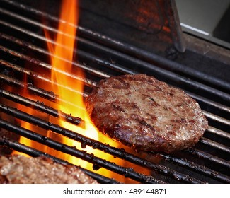 Burger pattie on a barbecue with flames