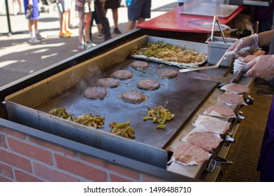 Burger patties and vegetables being cooked on a teppanyaki grill at a food stand.