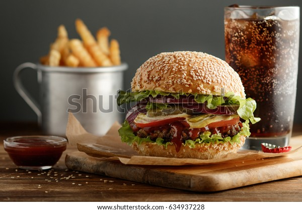 Burger with pickles, onion, served with golden French fries potatoes and fresh drink