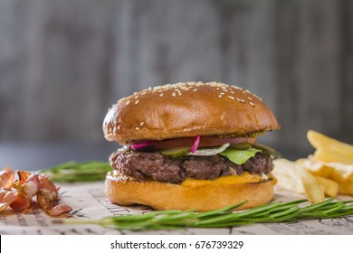 Burger with potatoes on cutting Board, telephoto