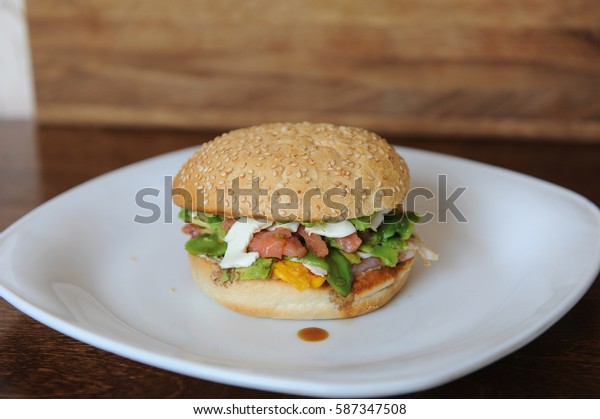 Burger with red fish, bacon, vegetables, cheese and berry sauce closeup. On a white plate on a wooden background