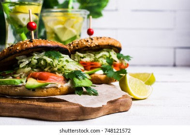 Burger with salted salmon and vegetables on wooden background. Selective focus.
