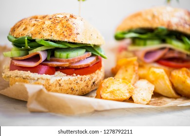 Burger sandwiches with ham , cucumber slices, lettuce and tomatoes and wedges potatoes