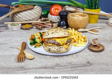 Burger au steak, au fromage, aux oignons, avocat accompagné de frites sur une assiette blanche, servi sur une planche en bois. Décoration sur fond de légumes.
