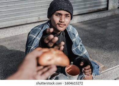 Burger from stranger. Smiling broadly homeless elderly man feeling cheerful while eating burger from stranger