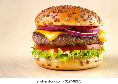 Burger with tomato , lettuce , mayonnaise , cheese , onion , ketchup and flax seeds on bun , yellow wooden background
