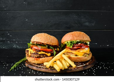 Burger with veal, cheese and vegetables. Fast food. On a wooden background. Top view. Free space for your text.