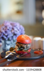 Burger. Wagyu beef burger with soft focus on the beef. Red buns with sesame.