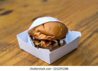 Burger in a white blank package on a wooden rustic table
