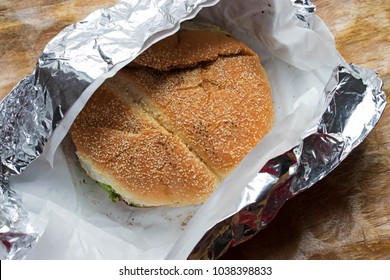 Burger wrapped in foil on rustic wood background. Shot from the top, with a seed bun. Could be a hamburger, or fish or chicken. Fast food or street food, hot and ready to unwrap and eat.Takeout burger