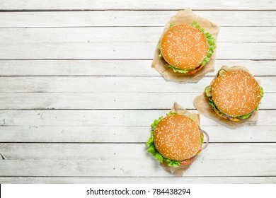 Burgers with beef, cheese and vegetables on paper. On a white wooden background.