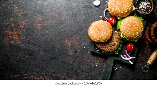 Burgers with beer and spices. On black rustic background