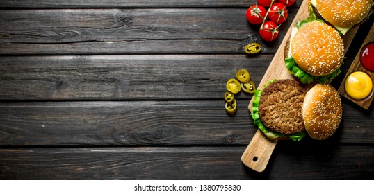 Burgers with different sauces,jalapenos and tomatoes. On black wooden background