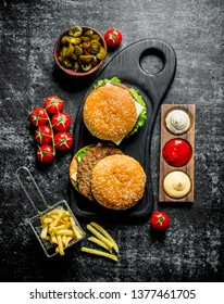 Burgers with fries,tomatoes and jalapenos in bowl . On black rustic background