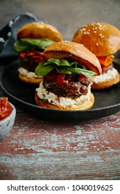 Burgers with grilled beef patties, cream cheese and spinach on classical bun.