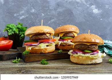 Burgers with juicy cutlet, fresh vegetables, crispy bun with sesame seeds on a wooden table. Traditional fast food.