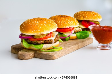 Burgers on wooden desk with tomato sauce - white kitchen background.  Selective focus. Copy space.