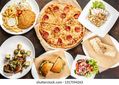 Burgers and pizza on wooden table, top view