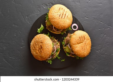 Burgers, pulled beef sandwiches with vegetables on black wooden board over stone background with copy space. Top view, flat lay