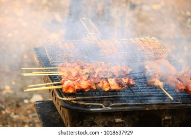 Burgers, shashliks and sausages on hot grill. Smoke. Backyard party or picnic background. Selective focus.