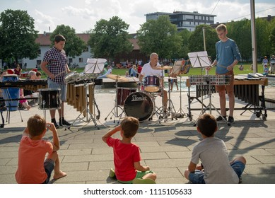 Burghausen,Germany-June 16,2018 : Children look on during a music school's public percussion concert in a park