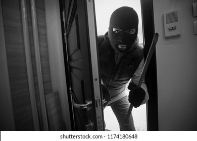 Burglar breaking door of house with crowbar