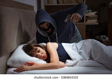 Burglar breaking into house at night to bedroom with sleeping wo